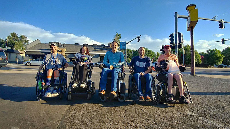 Five Craig grads in a line in their wheelchairs smiling.