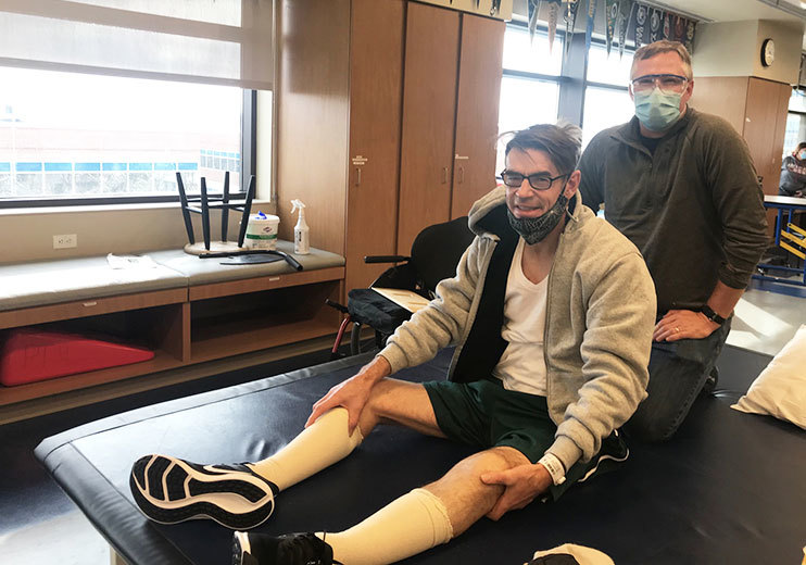 Andrew Hay sitting on physical therapy table at Craig Hospital with physical therapist standing behind him