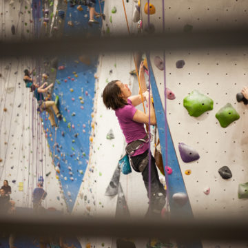 Craig Hospital grad Quinn Brett indoor rock climbs after her spinal cord injury.