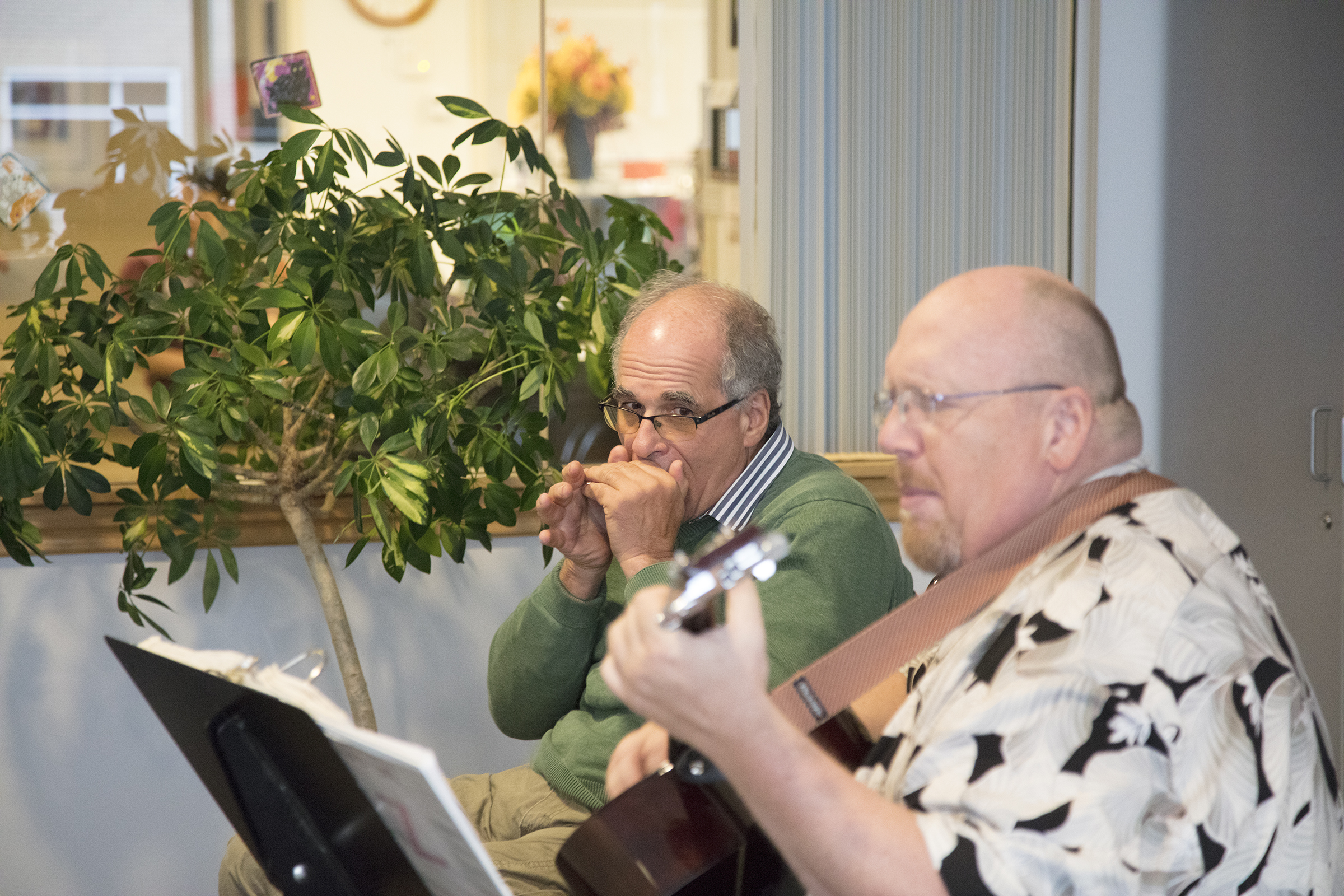 Jim Penta playing the harmonica while visiting Craig Hospital on Wish of a Lifetime trip years after spinal cord injury and traumatic brain injury rehabilitation